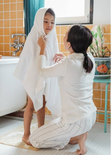 A mother wiping her daughter after a safe and comfy bath