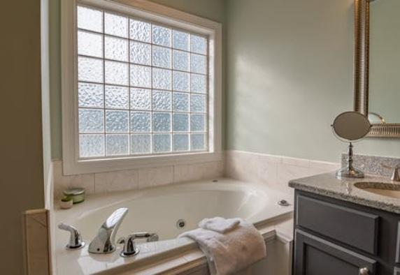 A bathroom with a ceramic tub and quartz counter