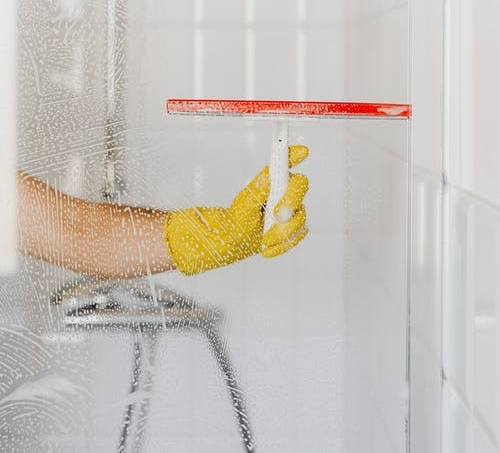 Person using squeegee to wipe a shower's glass wall